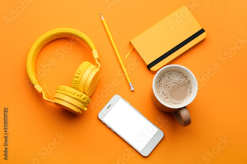 Obraz Modern mobile phone with headphones, notebook, cup of coffee and pencil on color background - fototapety do salonu