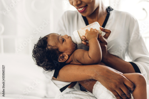 Fototapeta Portrait of enjoy happy love family african american mother playing with adorable little african american baby.Mom feeding bottle of milk to baby cute son in a white  bedroom.Love of black family  obraz