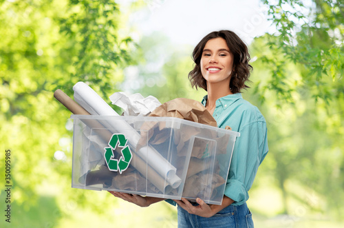 recycling, waste sorting and sustainability concept - happy smiling young woman holding paper garbage in plastic box over green natural background