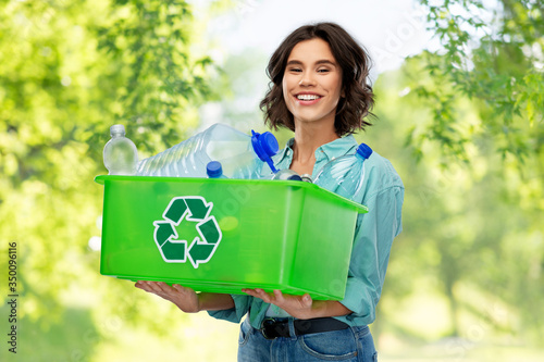 recycling, waste sorting and sustainability concept - smiling young woman holding box with plastic bottles over green natural background