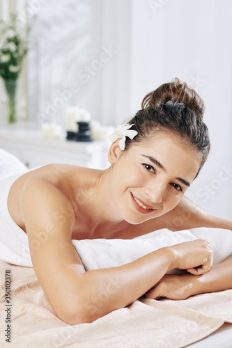 Attractive smiling young woman resting on bed in spa salon and looking at camera