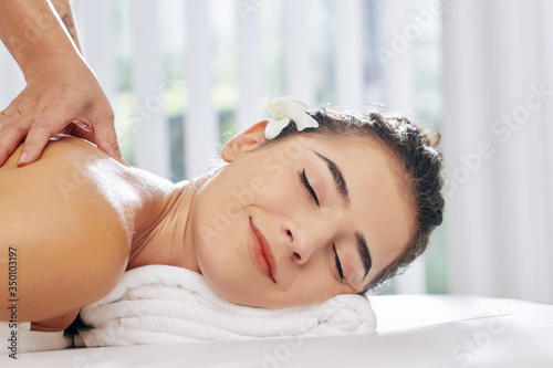 Pretty young woman smiling with pleasire when receiving relaxing back massage in spa salon