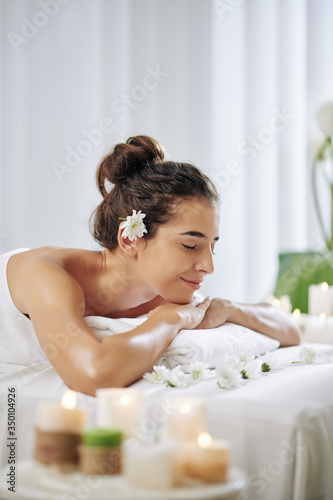 Beautiful attractive young woman enjoying smell of aroma candles in spa salon