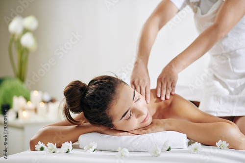 Pretty young woman relaxing on bed in spa salon and getting back massage