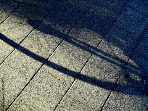 Carta da parati Shadow Of Bicycle Wheel On Paving Stone