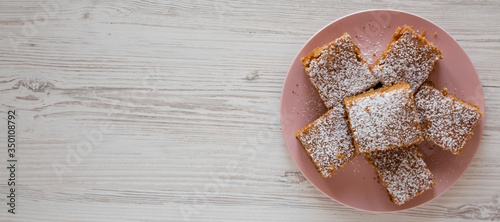 Homemade Tasty Applesauce Cake on a pink plate on a white wooden background, top view Canvas Print