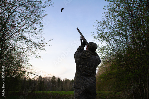 Fotografering a hunter takes aim at a flying woodcock late at night