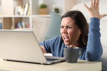 Angry Adult Woman Watching Video On Laptop At Home