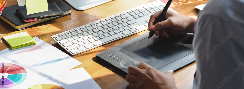Fototapeta Close up view of graphic designer working with drawing tablet and computer device