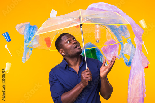 World Environment Day, plastic recycling problem and environmental disaster concept - Surprised african american man looking on trash on yellow background Canvas