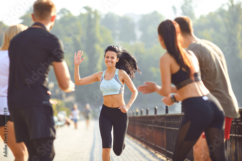 Obraz Girl runner runs fun with a group of friends in a park - fototapety do salonu