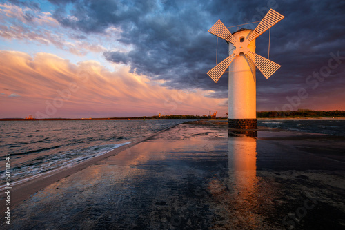 Obraz lighthouse in the shape of a windmill in Swinoujscie in Poland during the dramatic sunset - fototapety do salonu