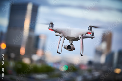 drone quadcopter with digital camera flying at city street