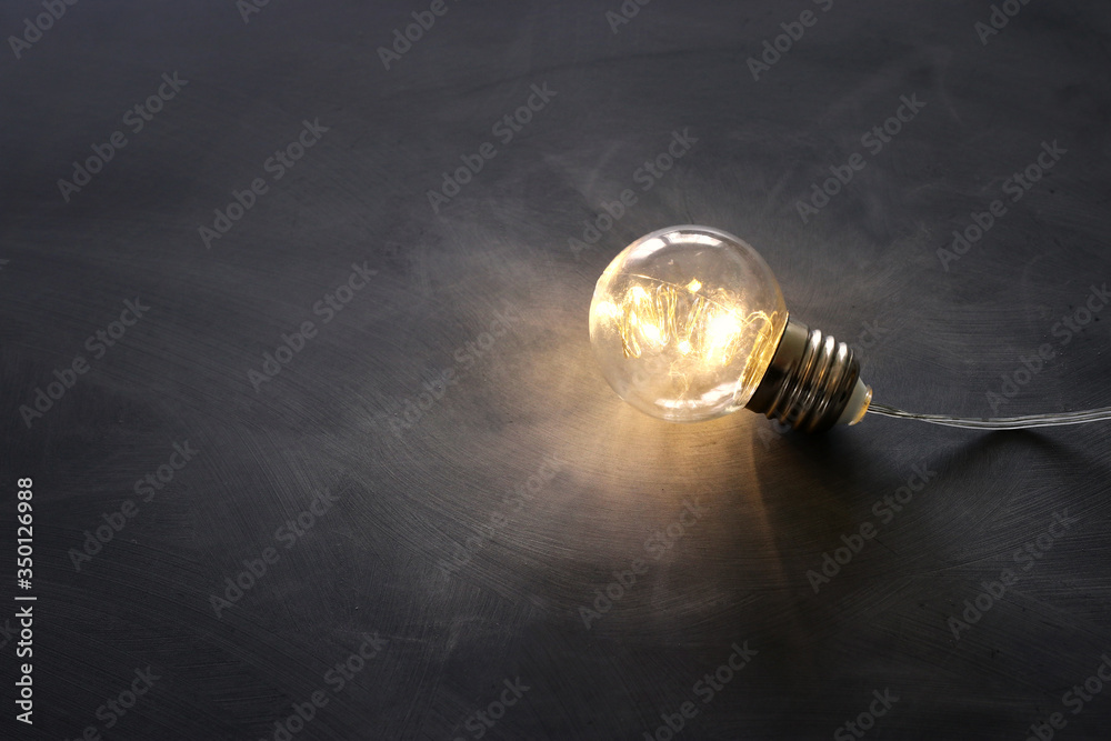 Fototapeta Education concept image. Creative idea and innovation. Light bulb as metaphor over blackboard