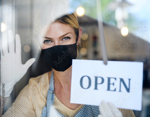 Coffee shop woman owner with face mask, open after lockdown quarantine. - 350127943