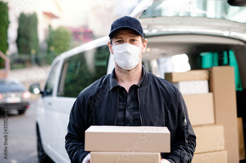 Delivery man courier with face mask delivering parcel boxes in town Fototapet