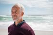 Leinwandbild Motiv Satisfied senior man thinking at beach