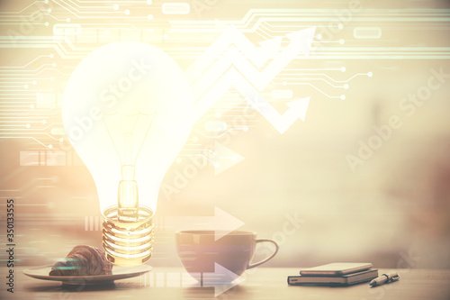 Double exposure of light bulb hologram over coffee cup background in office. Concept of idea