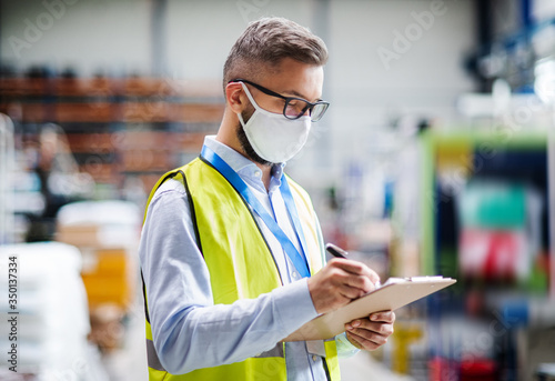 Foto Technician or engineer with protective mask working in industrial factory, writing