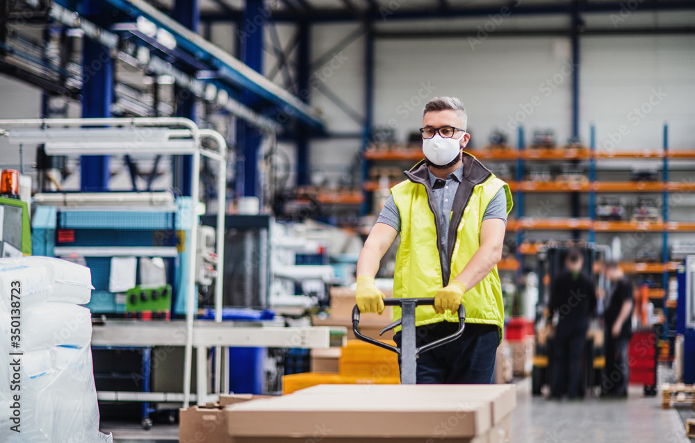 Fototapeta Man worker with protective mask working in industrial factory or warehouse.