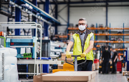 Fotografie, Obraz Man worker with protective mask working in industrial factory or warehouse