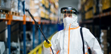 Man Worker With Protective Mask And Suit Disinfecting Industrial Factory With Spray Gun.