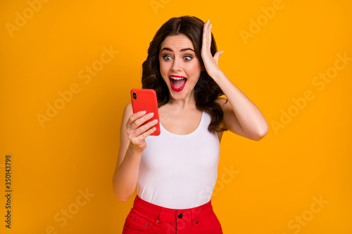 Fototapeta Photo of funky crazy millennial lady open mouth hold telephone read positive blog post comments hand on head wear casual white singlet red skirt isolated yellow color background obraz