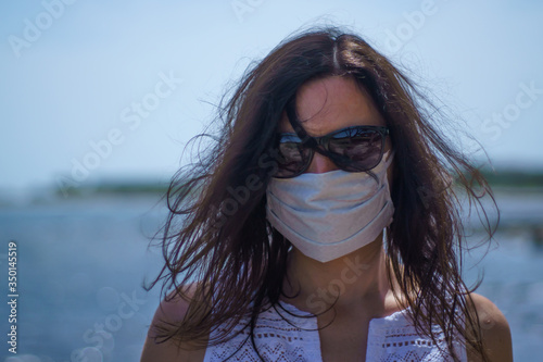 Tablou Canvas Coronavirus seaside holidays: half-length shot of a woman at the beach look at t