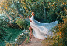 A Woman Is Standing On The Riverbank In A White Dress And A Raincoat With Feathers. Queen Of Swans. A Fashionable Cloak For Wedding Events Embroidered With Silver And Stones Flutters In The Wind.