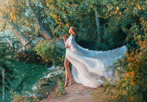 Fototapeta A woman is standing on the riverbank in a white dress and a raincoat with feathers. Queen of swans. A fashionable cloak for wedding events embroidered with silver and stones flutters in the wind. obraz