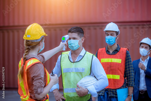 Obraz Woman worker used a medical Digital  temperature Thermometer to check staff body temperature before start work in factory ,they wearing face mask the concept of a corona virus [Covid-19] screening. - fototapety do salonu