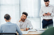 Selective focus of african american man looking at camera near business people in office