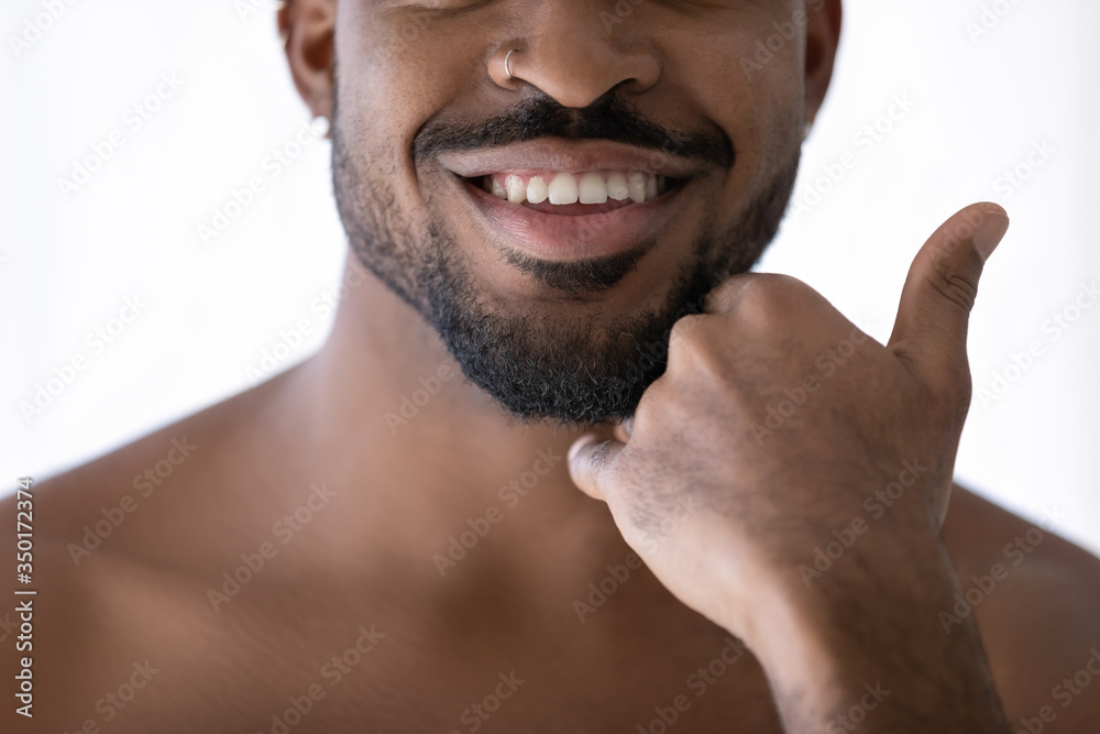 Fototapeta Crop close up of happy african American young man touch beard stubble after shaving in bathroom, smiling biracial male satisfied with shaved bristle after shower in bath, body hygiene concept