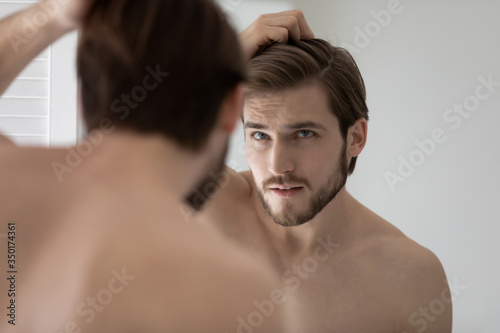 Anxious young Caucasian man look in mirror in bathroom touch check head worried Tableau sur Toile