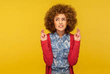 Waiting Fortune. Portrait Of Woman With Curly Hair Crossing Fingers For Good Luck, Making Wish And Hoping For Win, Clenching Teeth In Anticipation Of Success. Studio Shot Isolated On Yellow Background