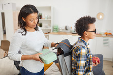 Side View Portrait Of Young African-American Woman Packing School Lunch While Sending Son To School
