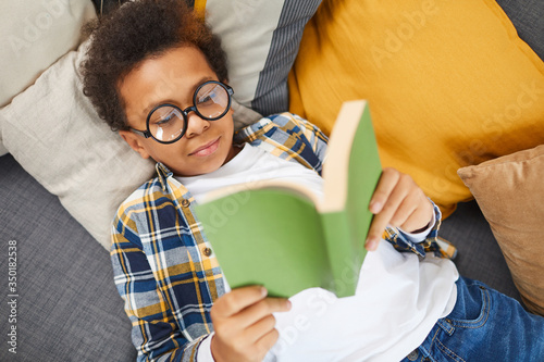 Cuadros en Lienzo Above view portrait of cute African boy wearing big glasses reading book while l