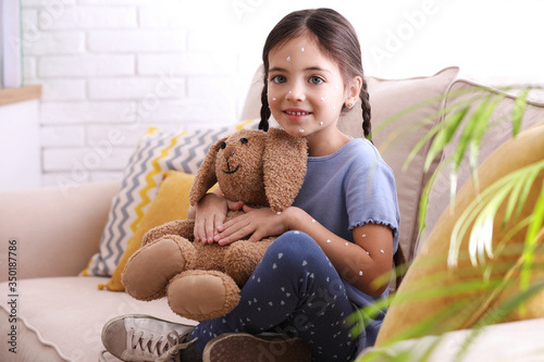 Little girl with chickenpox playing at home Canvas Print