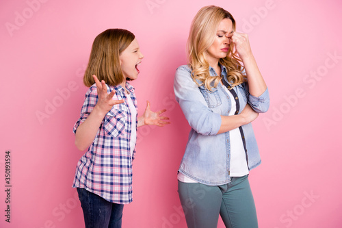 Obraz Frustrated two people aggressive kid girl yell scream mother touch nose suffer headache hate family misunderstanding wear denim jeans checkered plaid shirt isolated pastel color background - fototapety do salonu