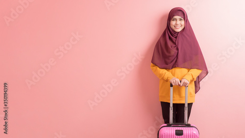 Fotografía muslim woman with hijab is holding luggage on pink background , people travel co