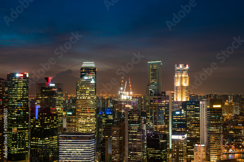 Fototapeta Picturesque panoramic view of Singapore city at night time. Financial and trading center hub in Asia region. Concept of success. Modern buildings in high-tech world.