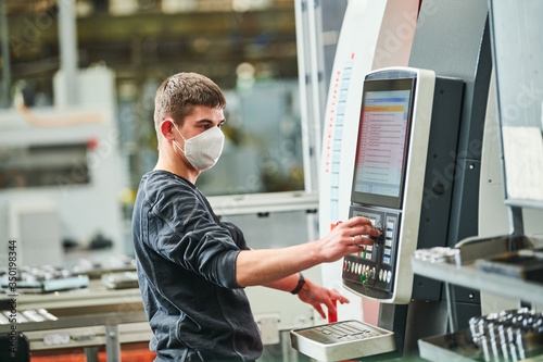Industrial worker operating cnc machine in protective mask at metal machining in Canvas Print