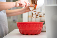 Housewife Pouring Chocolate Into A Red Silicone Mold To Make A Delicious Cake After Using The Mixer On The Kitchen Table At Home