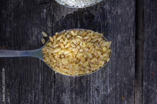 bulgur in a tablespoon on a wooden background Tapéta, Fotótapéta