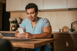 young mixed race man using smartphone on kitchen during quarantine