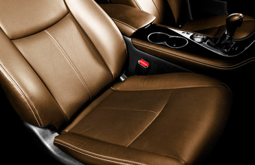 Luxury car brown leather interior. Part of leather car seat details with stitching. Comfortable perforated orange leather seats. Brown perforated leather. Car inside