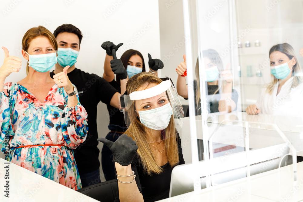 Fototapeta gruppo affiatato di lavoro con in primo piano la segretaria fornita di tutti i dispositivi di protezione e il resto della squadra con mascherina chirurgica