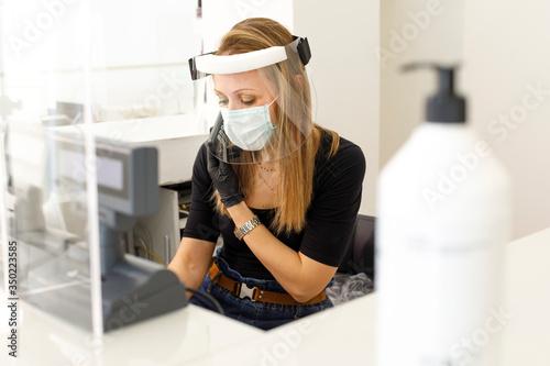 segretaria di un locale nella postazione di lavoro alle prese con il telefono e Fototapet