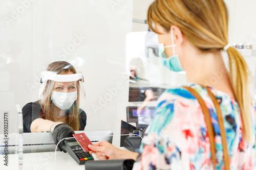 Obraz dentro un locale commerciale la cliente paga alla cassa con carta di credito munita di mascherina e separata dalla cassiera da un separatore di plexiglass  - fototapety do salonu