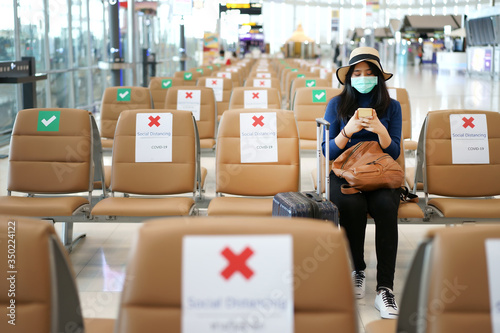 Young Asian traveler sitting at the international airport during COVID-19 disease crisis with social distancing and wearing mask Canvas Print
